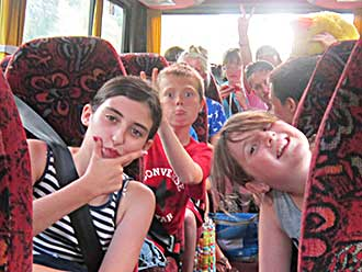 Children on a bus making faces at camera