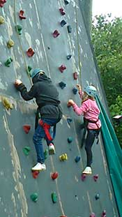 Siblings climbing wall